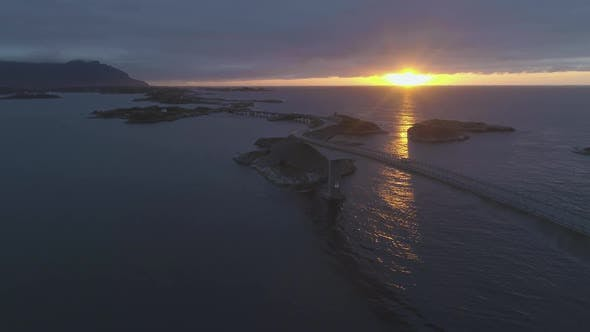 Cover Image for Atlantic Ocean Road in Norway at Summer Sunset. Car Is Passing on Storseisundet Bridge. Aerial View