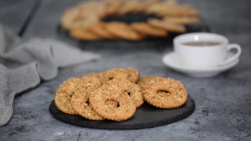 Shortbread Cookie Ring with Peanuts and Cup of Tea on Wooden Table