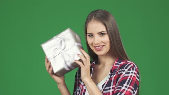 Thumbnail for Stunning Happy Young Woman Shaking Present Box Guessing What Is Inside