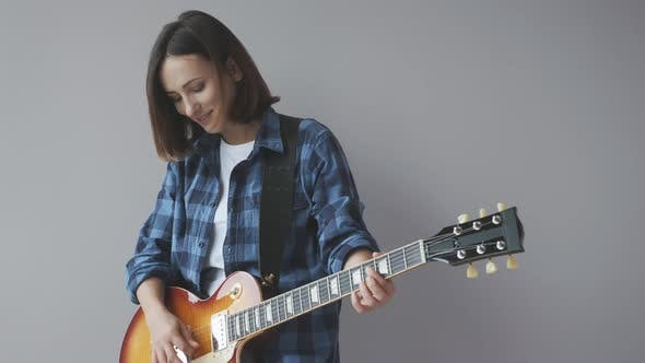 Thumbnail for Woman playing electric guitar. Attractive girl with electric guitar playing jazz and blues songs.
