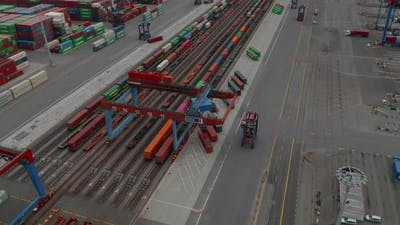 Aerial View of Forklift Driving in Commercial Cargo Terminal By Colorful Cargo Containers