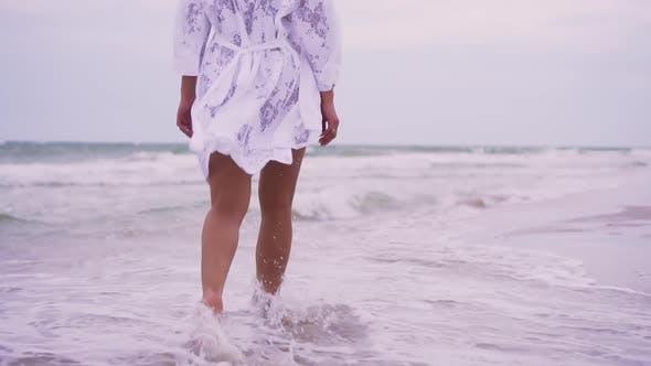 Mädchenspaziergänge am Strand auf dem Hintergrund des Meeres