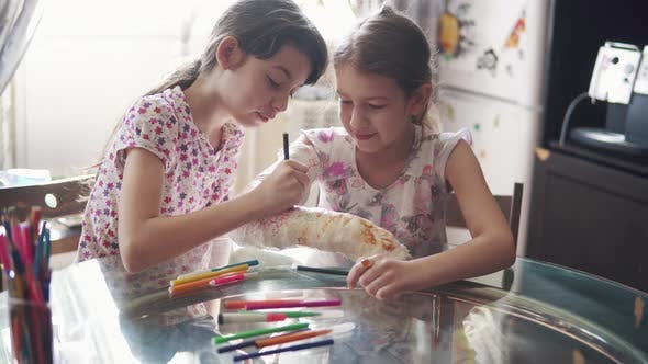Cover Image for Children Draw Together on a Plastered Arm in a Bandage, Sister Encourages and Cares for a Sick