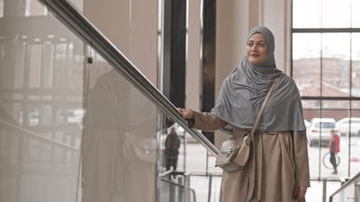 Arabic Woman on Escalator in Office
