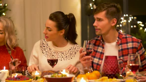 Cover Image for Happy Friends Having Christmas Dinner at Home