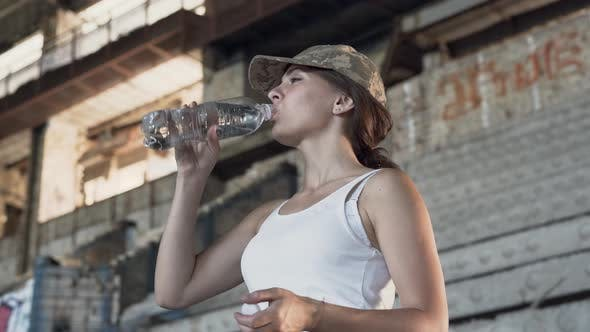 Thumbnail for Portrait of Attractive Young Woman in Military Cap Drinking Water From the Bottle in Dusty Dirty