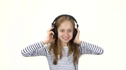 Girl Listens Music on Headphones and Showing Tongue, White Background