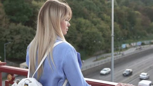 Business Girl Stands on a Pedestrian Bridge and Looks at the Stream of Cars