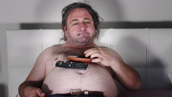 Fat Man Eating In Bed Watching Television 6