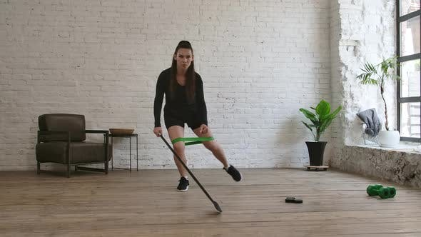 Thumbnail for Self Isolation Concept: A Woman Hockey Coach Practicing Sliding Movements with a Hockey Stick