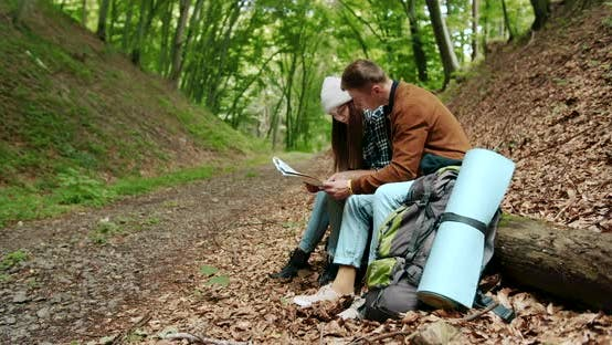 Thumbnail for Tourists with Map Resting Sitting in Forest