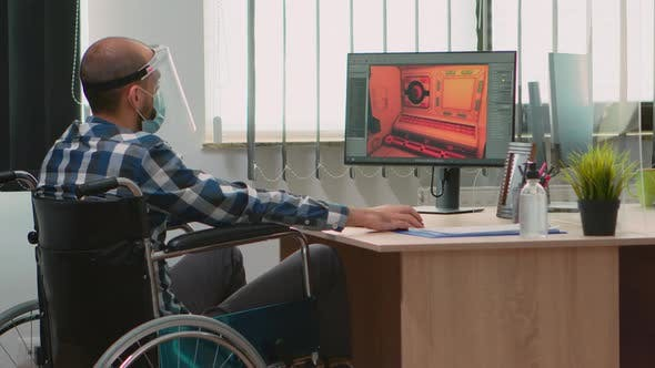 Handicapped Game Developer in Wheelchair with Mask Working