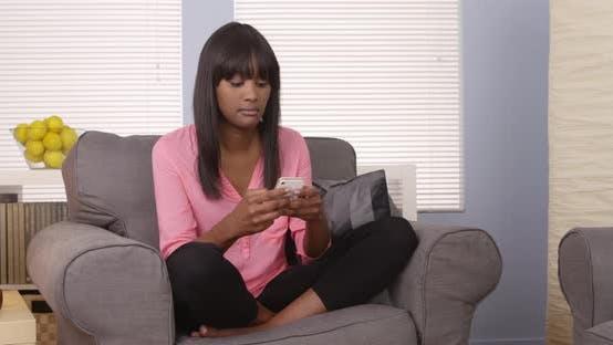 Thumbnail for Cute black woman using smartphone on couch