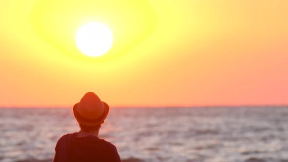 Thumbnail for Young Guy in a Hat Watching the Sunset By the Ocean. The Male Traveler Enjoys the View of the East