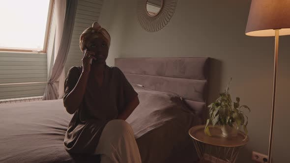 Young African American Woman Chatting on Phone in Bedroom