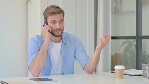 Angry Young Creative Man Talking on Smartphone in Office