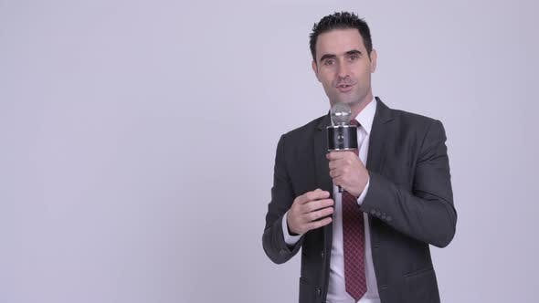 Thumbnail for Handsome Businessman Presenting Something with Microphone