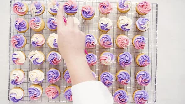 Flat lay. Dusting small vanilla cupcakes with food glittery dust.