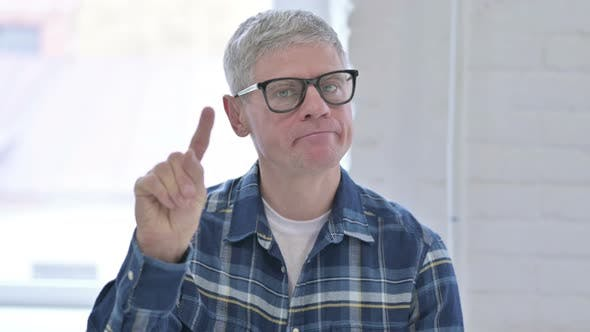 Thumbnail for Portrait of Middle Aged Male Designer Saying No By Finger Sign