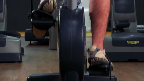 Thumbnail for A Fit Man Trains on an Exercise Bike in a Gym - Closeup on Feet From Behind
