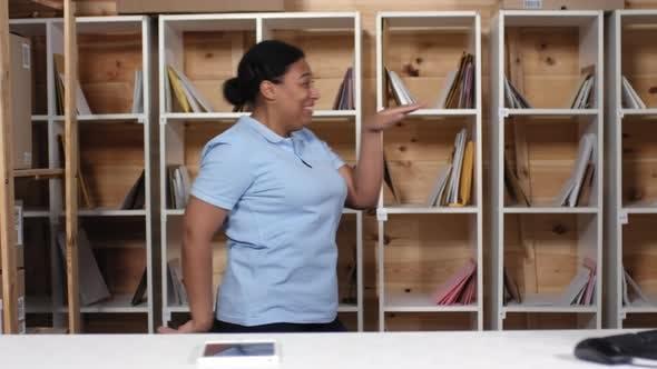 Thumbnail for Uninhibited Black Female Clerk Dancing in Post Office