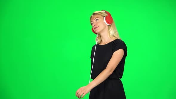 Thumbnail for Cheerful Girl Walks in Big Red Headphones and with a Smartphone, Switches Music and Dancing, Chroma