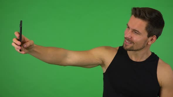 Thumbnail for A Young Handsome Athlete Takes Selfies with a Smartphone - Green Screen Studio