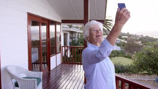 Thumbnail for Frau unter Selfie mit Handy auf dem Balkon zu Hause 4k