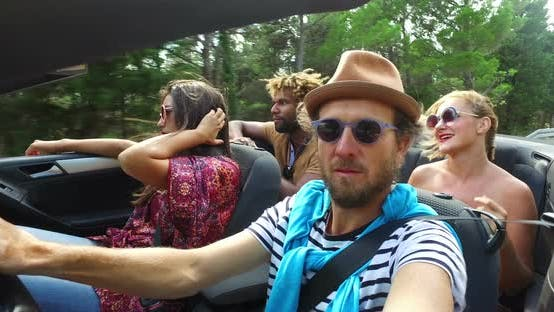 Bearded hipster man with a hat driving his friends in convertible