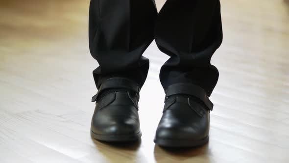 Thumbnail for Mann in schwarzen Schuhen und Hosen macht Schritte vorwärts und geht weg