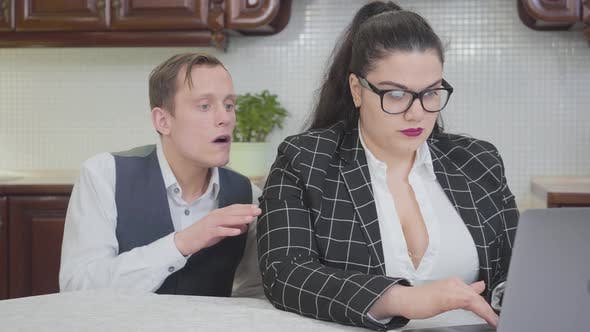 Young Confident Plump Woman Working with Laptop at the Table. A Timid Young Man Touches Her Shoulder