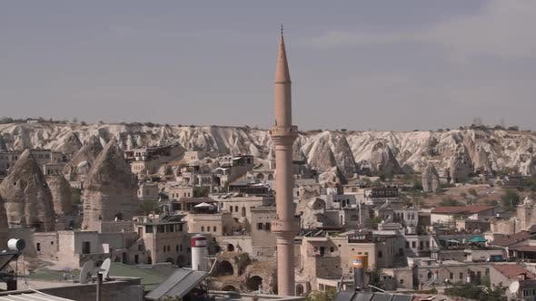 High Minaret of Mosque with Sharp Spire By Stone Buildings