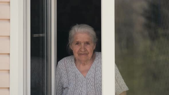 Thumbnail for The Old Woman Looks Out of the Window and Smiles.
