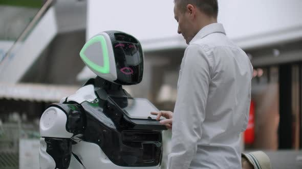 A Man in a Shirt Communicates with a White Robot Asking Questions and Pressing the Screen with His