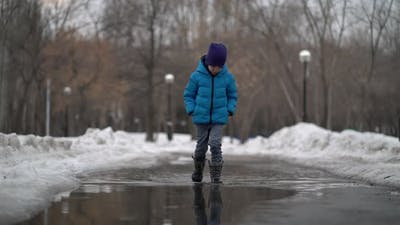 Boy Walking in a Puddle at Winter