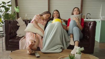 Group of Female Friends Watching Drama or Melodrama on TV at Home