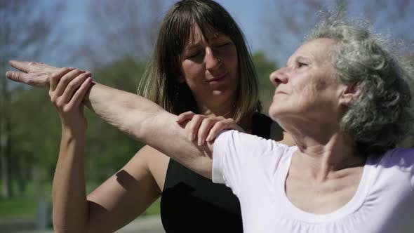 Therapeutic Fitness Instructor Helping Senior Lady