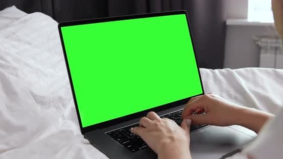 Young girl searching internet sitting in modern hotel room. Green screen monitor