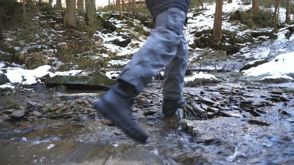 Cover Image for Young Backpacker Walks Over Stones on Mountain River at Pine Forest. Unrecognizable Hiker with