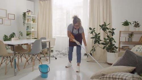 Woman in Apron Mopping Floor