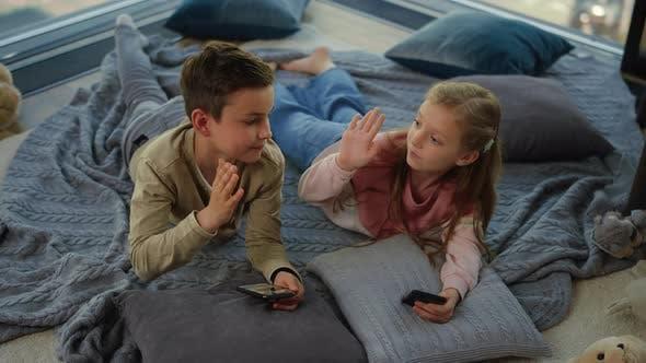 Cute Siblings Using Smartphones Indoors. Children Giving High Five.