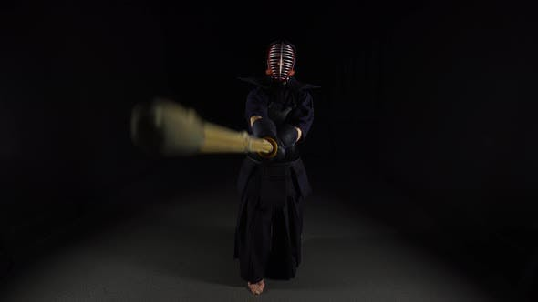 Thumbnail for Strong Kendo Guru Practicing Martial Art with the Bamboo Bokken on Black Background.