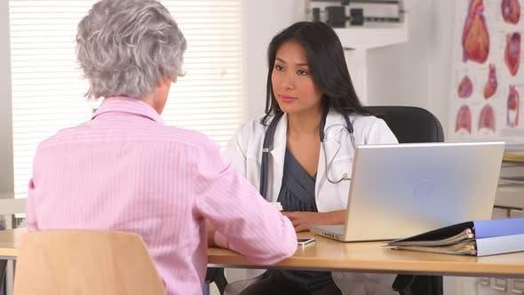 Thumbnail for Reife Frau erklärt gesundheitliche Fragen zu japanischen Arzt