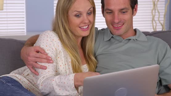 Thumbnail for Couple looking for vacation getaway on laptop
