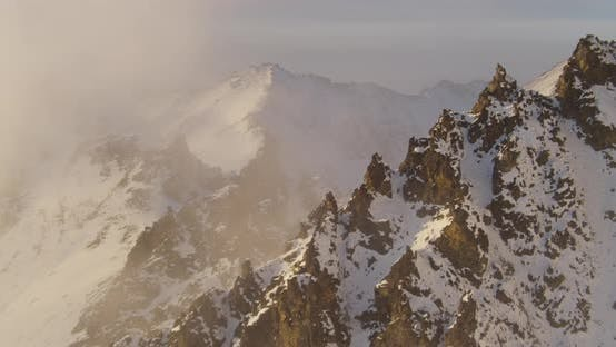 Thumbnail for Helicopter flying over brown forest and river with mountains in background, golden hour, aerial dron