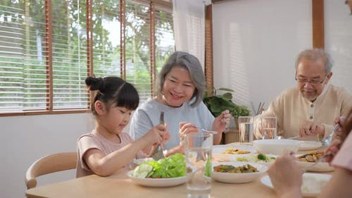 Asian Big happy family spend time have lunch on dinner table with young little kid together at home
