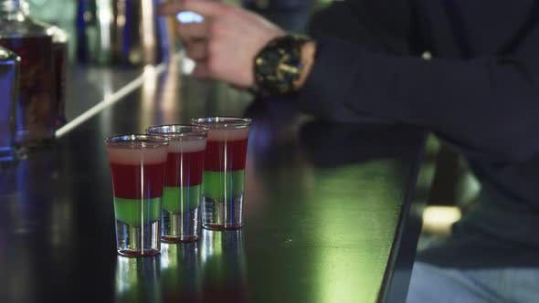 Thumbnail for Selective Focus on Three Shots on the Bar Table Man Using His Smart Phone on the Background
