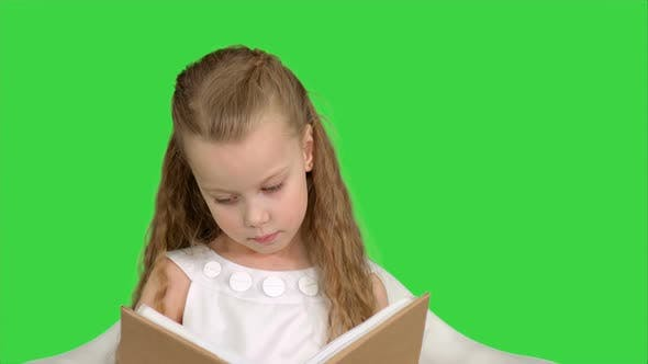 Thumbnail for Pretty Little Girl Sitting with Book and Reading on a Green Screen, Chroma Key