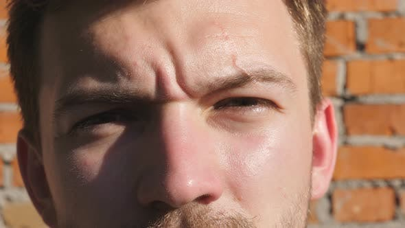 Thumbnail for Portrait of Male Face Illuminated By Sun Looking Into Camera on Blurred Brick Wall Background. Brown
