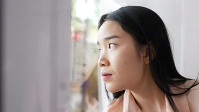 Woman stay home and looking outside